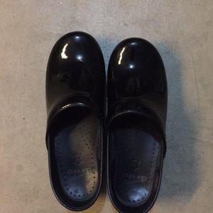 Dansko black patent leather clogs.